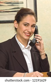 Attractive brunette businesswoman is busy on the phone.