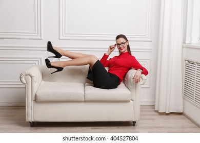 Attractive brunette businesswoman in eyeglasses with red lips lying on white sofa as symbol of sex, seduction, business, work, success, style, leadership, management, entrepreneur