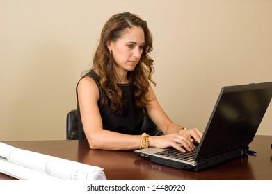 Attractive brunette businesswoman at her desk, hard at work on her notebook computer.