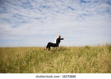 attractive brunette businesswoman relaxing on meadow