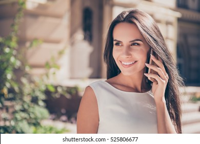 Attractive brunette businesswoman talking on mobile phone with client.