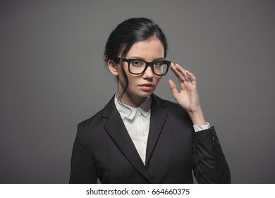 attractive brunette businesswoman wearing black suit and eyeglasses, isolated on grey