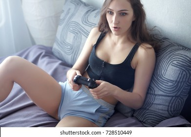 Attractive brunette caucasian woman in home wear, sit at the bed, play video-games with game-pad, look at TV screen with different emotions