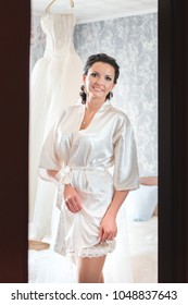 An attractive brunette in a dressing gown and bridal garter admiring her look in the mirror while preparing for her wedding