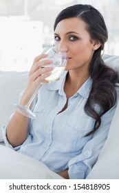 Attractive brunette drinking white wine sitting on sofa in her living room