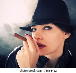 Attractive brunette in a felt hat smoking a cuban cigar