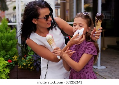 An attractive brunette female dressed in a white dress and sunglasses and cute teenage girl eating ice cream on a street.