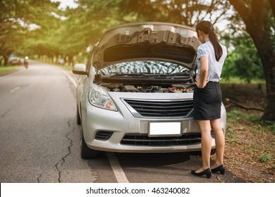 attractive brunette in front of her car broken down car.