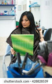 Attractive brunette girl is choosing hair color from the catalog in hair salon.