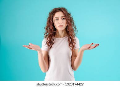 Attractive brunette girl with curly hair isolated over blue turquoise background with unhappy and sad face. Hangover concept