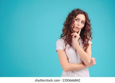 Attraktives Brautmädchen mit lockigem Haar einzeln auf blauem türkisblauem Hintergrund, Denken und Entscheiden