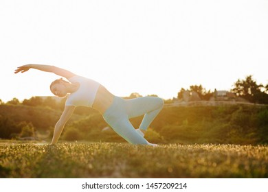 Attractive brunette girl relaxing in nature and practicing yoga in sunset. Empty space