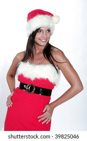 Attractive brunette girl in santa cloth smilling in front of a white background