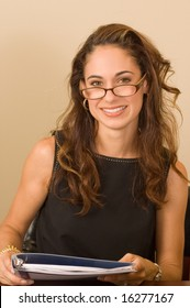 Attractive brunette with glasses reading a report in a binder, smiling at the camera