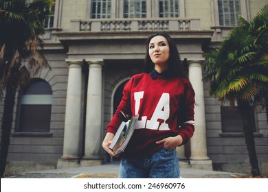 Attractive brunette hair student standing on university entrance background holding books