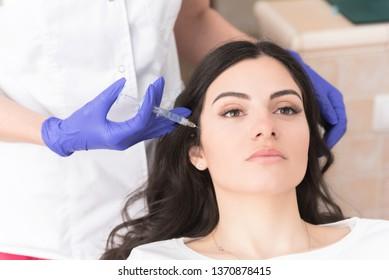 Attractive brunette having cheek fillers in modern medical office, Aesthetic corrective medicine concept