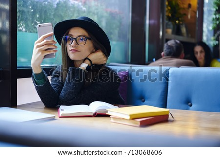 66527bda8d4 Attractive brunette hipster girl in eyewear reading news from network  sitting in cozy place