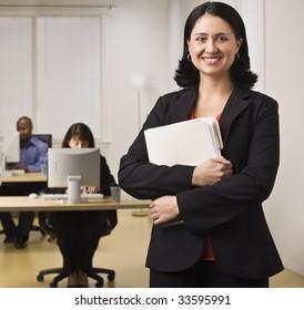 Eine attraktive Brünette hält Dateiordner und lächelt die Kamera an. An den Schreibtischen hinter ihr arbeiten Leute an Computern. Viereckige Komposition.