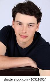 Attractive brunette male model on grey background wearing black