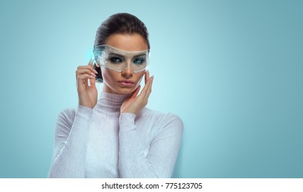An attractive brunette model in futuristic office with virtual holographic glasses, smooth background with copyspace