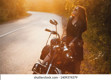 attractive brunette motorcyclist standing near a motorcycle On the Sunset. adventure concept