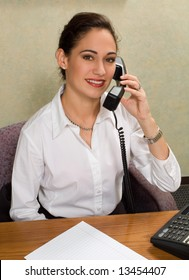 Attractive brunette on the telephone in her office.