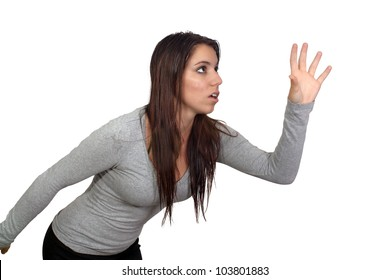 An attractive brunette reaching for or grabbing something.  Isolated on a white background with generous copyspace.