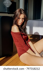 Attractive brunette in red bodywear sitting on floor in sunlight looking provocatively at camera.
