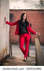 Attractive brunette in a red pant suit