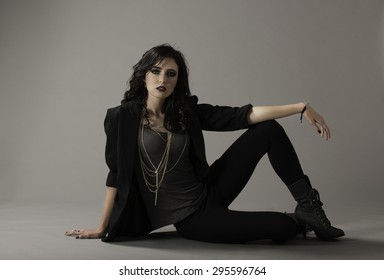 Attractive brunette in rocker fashion posing in black leggings with boots