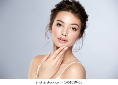 attractive brunette with shiny highlighters and glossy lips touching her chin, pretty woman with natural mua and perfect hairstyle