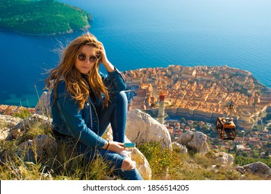 Attractive brunette sitting on the Srd hill above the city of Dubrovnik, observing the city in the distance. Wind blowing her hair above the ancient famous landmark town. Cablecar going down