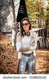 Attractive brunette with sunglasses and wireless headphones in front of the mountain cabin in autumn