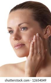 attractive brunette woman applying cream