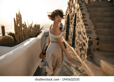 Attractive brunette woman in beige dress holds straw hat and runs along path in old beautiful city. Happy girl smiles and looks into camera.