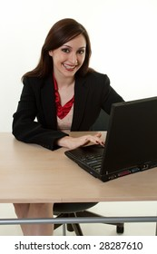 Attractive brunette woman in business suit sitting at a desk and looking at a computer screen