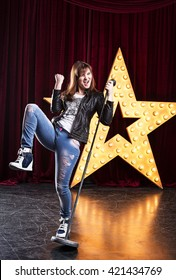 attractive brunette woman in jeans and a leather jacket singing on stage at the microphone. Against the background of a large glowing star.
