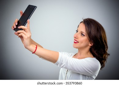 Attractive brunette woman with long hair standing sideways taking a selfie on her mobile phone smiling for the camera, head and shoulders over grey with vignette