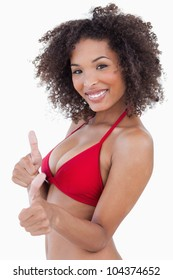 Attractive brunette woman looking at the camera while putting her thumbs up