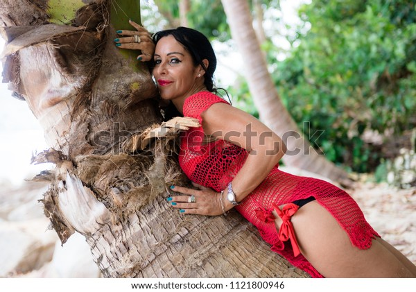 attractive brunette woman lying on a palm tree in a swimsuit as in the famous advertisement