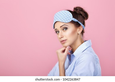 attractive brunette woman in pajamas and mask for sleeping on a pink background