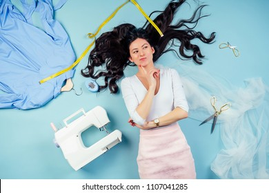attractive brunette woman seamstress tailor ( dressmaker) dreams and thinks about a new collection of clothes on the floor with sewing machine and measuring tape on a blue background in the studio.