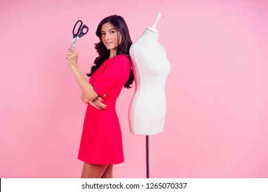 attractive brunette woman seamstress tailor ( dressmaker) in a nice dress hugging a mannequin and holding scissors in his on a pink background in the studio