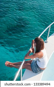 Attractive brunette woman sitting on deck of the yacht, looking at sea