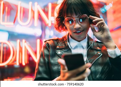 Attractive brunette woman in spectacles searching songs in network for downloading while standing near night city lights,positive hipster girl watching online video on phone using earphones outdoors