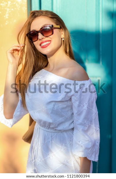 Attractive, brunette woman standing in fron of a colorfull door in soft summer light