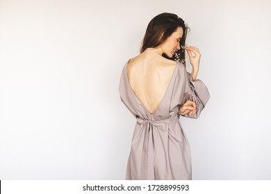 Attractive brunette woman wear lilac cotton cocktail dress featuring long lantern sleeves. Model wearing casual or evening outfit and playing with gypsophila. Dress with cut back.