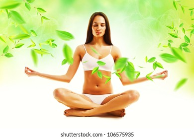 attractive brunette woman in yoga pose and leaves