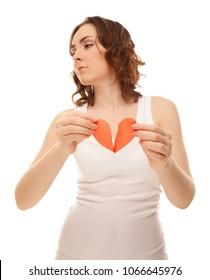 Attractive brunette young girl holding broken paper red valentine heart
