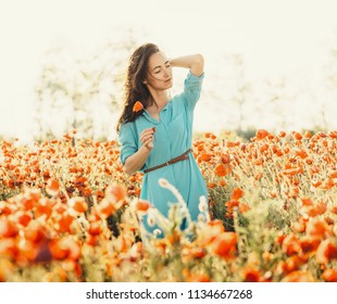 Attractive brunette young woman walking in poppies meadow in summer.